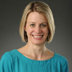 Portrait of Dr. Peppard, with chin-length blonde hair, a teal shirt, smiling.